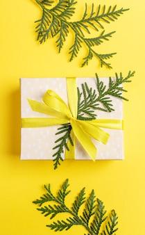 Natale, capodanno, san valentino sfondo giallo con confezione regalo fai da te decorato con nastro giallo con fiocco e rami verdi di arborvitae su sfondo giallo brillante. vista dall'alto. orientamento verticale.