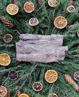 Natale, capodanno vacanza invernale composizione in stile vintage. pezzo di corteccia di albero su rami di abete verde decorato con fette e coni d'arancia essiccati.