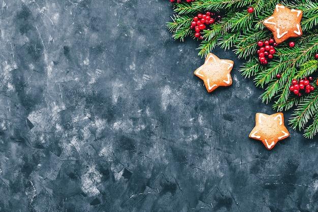 Natale e capodanno con bacche invernali, biscotti allo zenzero a forma di stella e rami di abete in uno stile scuro. spazio libero e vista dall'alto.