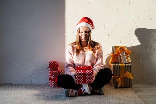 Natale e capodanno giovane donna in santa cappello circondato da regali