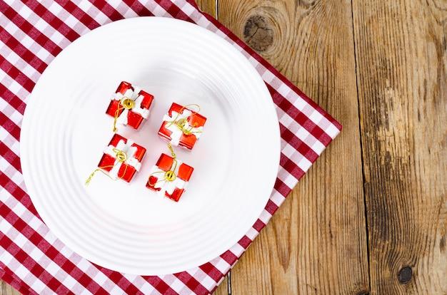 Concetto di natale e capodanno. piatto bianco, tovaglia rossa. foto di studio