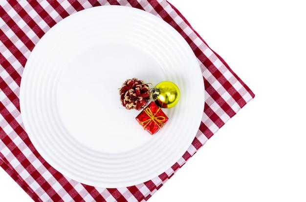 Concetto di natale e capodanno. piatto bianco, tovaglia rossa.
