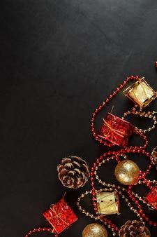 Sfondo scuro di natale o capodanno con decorazioni rosse e oro per l'albero di natale con spazio libero.