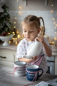 Natale norning, piccola bella ragazza sorridente in pigiama versa il tè dalla teiera nella tazza al tavolo della cucina.