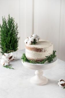 Torta di natale nudo con crema bianca e decorazioni natalizie, immagine di messa a fuoco selettiva