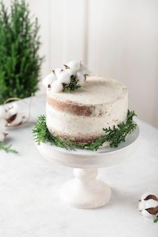 Torta nuda di natale con crema bianca e decorazioni natalizie, immagine di messa a fuoco selettiva