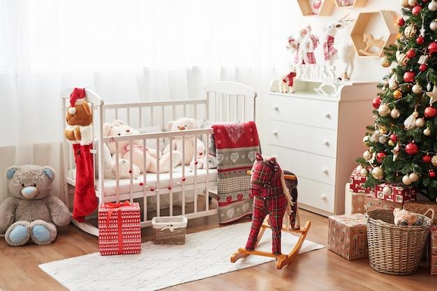 Scuola materna di natale, decorazioni natalizie nella camera dei bambini, sala giochi per bambini decorata per il nuovo anno, camera dei bambini bianca. giocattoli e regali di natale nella camera dei bambini, letto bianco con peluche