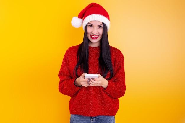 Congratulazioni online di natale. donna in cappello della santa utilizzando tablet mobile per videochiamata amici e genitori.