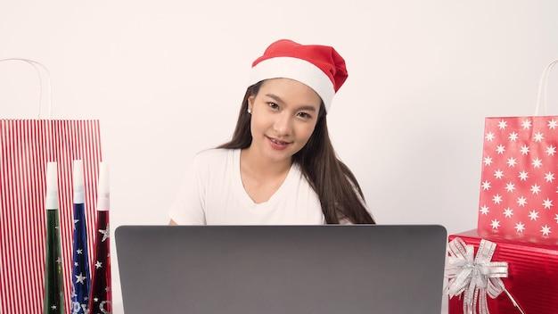 Celebrazione delle vacanze di natale online con una donna asiatica adolescente festa di natale e capodanno in isolamento coronavirus quarantena covid nuova normale comunicazione a distanza sociale comunicazione remota rimanere a casa vocazione
