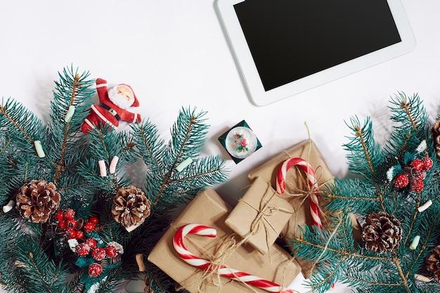 Natale shopping online sfondo schermo tablet con spazio copia rami di abete regali su ba...