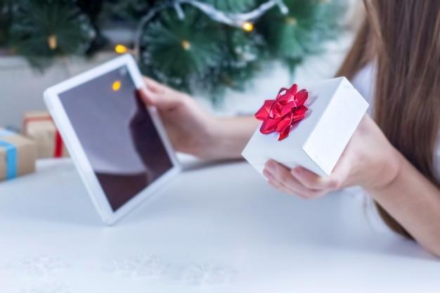 Shopping online di natale. la donna vaga in maglione bianco sta acquistando i regali di natale con il computer portatile