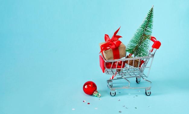 Concetto di acquisto online di natale. carrello con regali, decorazioni natalizie, albero di natale su sfondo blu.