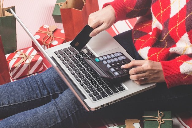Shopping online di natale. acquirente femminile con laptop, prepararsi alla vigilia di natale, seduto tra scatole e pacchetti di regali. saldi per le vacanze invernali