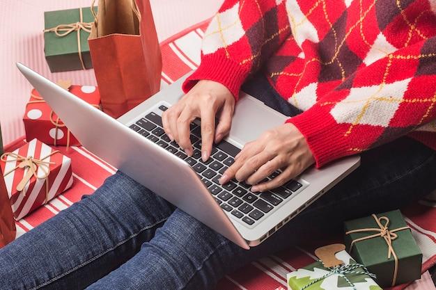 Shopping online di natale. acquirente femminile con laptop, prepararsi alla vigilia di natale,