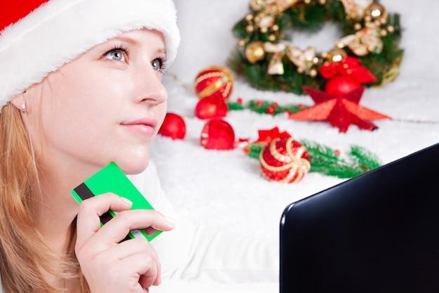 Lavoro e istruzione di acquisto in linea di natale donna con il computer portatile a casa in cappello della santa saldi di vacanze invernali