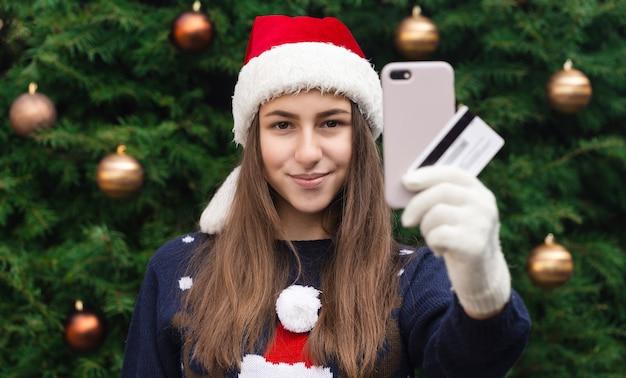 Shopping online di natale. una giovane ragazza in un cappello di babbo natale e un maglione blu che tiene smartphone. natale durante il coronavirus