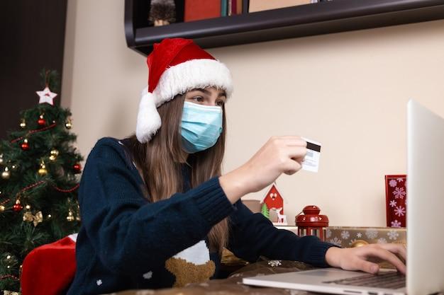 Shopping online di natale. una giovane ragazza con un cappello di babbo natale e un maglione blu in una maschera medica si siede vicino a un computer portatile. la stanza è addobbata a festa. natale durante il coronavirus
