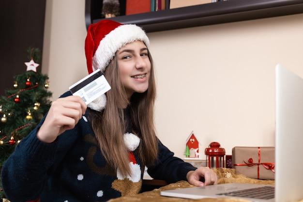 Shopping online di natale. una giovane ragazza con un cappello di babbo natale e un maglione blu si siede vicino a un computer portatile. la stanza è addobbata a festa.