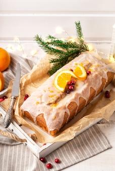Torta natalizia all'arancia con mirtilli rossi e glassa di zucchero su fondo di legno rustico