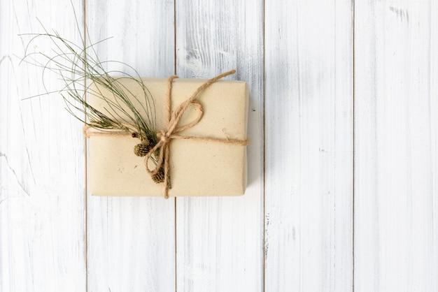 Ornamento di natale scatola regalo marrone e pigne fresco ramo verde su bianco sullo sfondo di legno, piatto laici