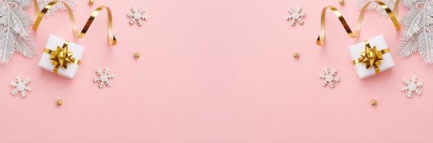 Ornamento di natale con decorazioni in oro su sfondo rosa pastello.