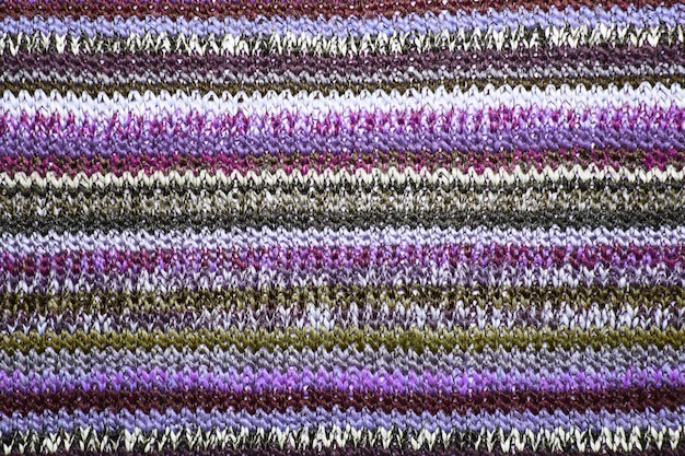 Maglia ornamentale natalizia con strisce. trama di sfondo maglione lavorato a maglia. fondo strutturato del tessuto a maglia reale. texture maglione colorato