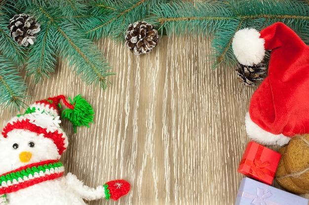 Ornamenti natalizi, rami di abete e pupazzo di neve a maglia natalizia