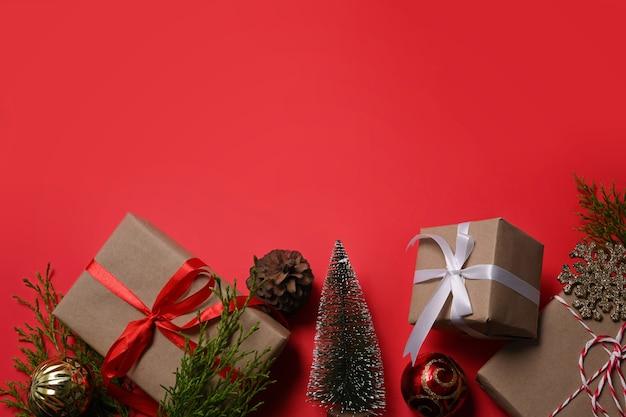 Ornamenti di natale, scatole regalo e rami di abete su sfondo rosso. copia spazio.