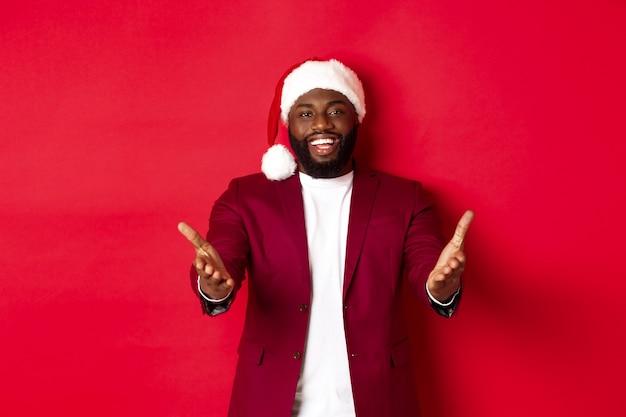 Natale, festa e concetto di vacanze. felice uomo nero con cappello da babbo natale ti dà il benvenuto, indicando le mani alla telecamera con un sorriso compiaciuto, in piedi su sfondo rosso
