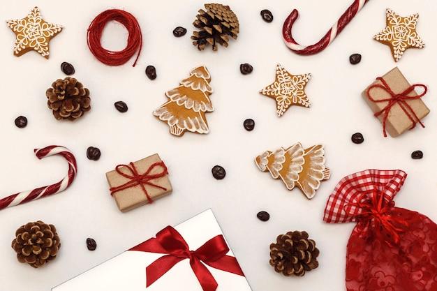 Motivo natalizio con lecca-lecca pan di zenzero e pigne su sfondo bianco