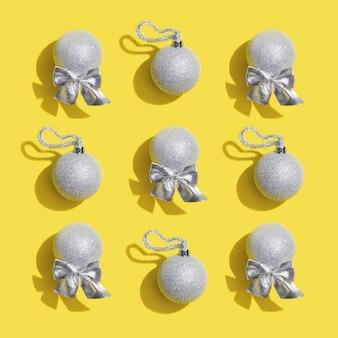 Motivo natalizio con palline argentate lucide su giocattoli gialli di capodanno con ombra scura