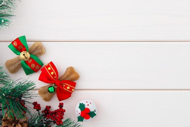 Natale per animali domestici. ossa di cani che avvolgono in archi di natale, campana di tintinnio su legno bianco.