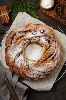 Rotolo di torta di natale con cannella e zucchero a velo su un vecchio fondo scuro di cemento o pietra
