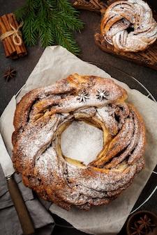 Rotolo di torta di natale con cannella e zucchero a velo su un vecchio cemento scuro