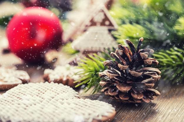 Natale. pasticceria e decorazione della palla di natale della pigna nell'atmosfera nevosa.