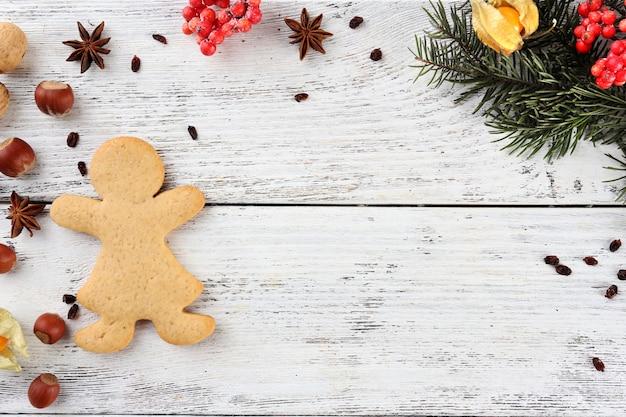 Rametto di pino natalizio con spezie e pan di zenzero su fondo di legno colorato