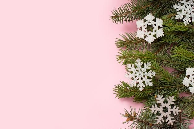 Cartolina di natale rosa con albero di abete e fiocchi di neve, felice anno nuovo sfondo, copia spazio