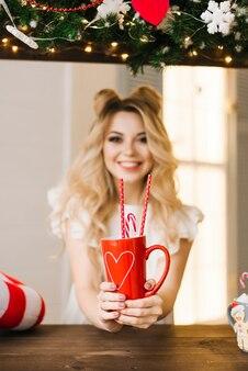 Ritratto di natale di bella ragazza con una tazza rossa su una barra di natale. anno nuovo e concetto di natale. messa a fuoco selettiva