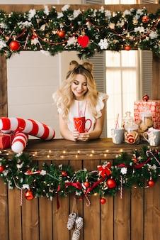 Ritratto di natale di bella ragazza con una tazza rossa su una barra di natale.