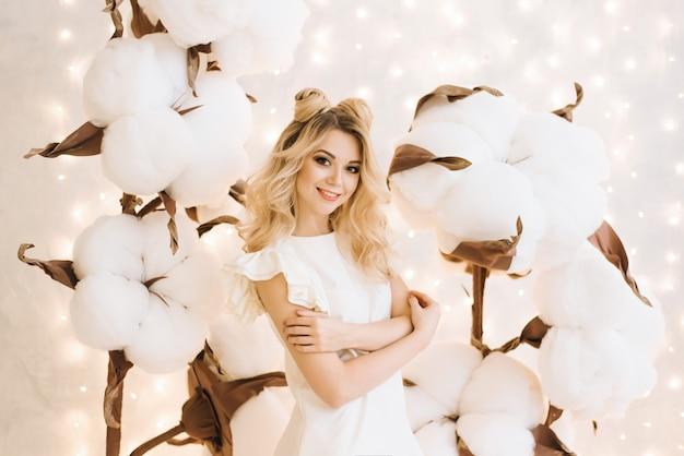 Ritratto di natale di una bella ragazza con i capelli bianchi. una donna attraente tra i grandi rami del cotone