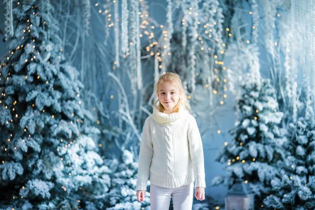Il ritratto di natale dello studio dell'interno della ragazza bionda felice del bambino, inverno nevoso ha decorato l'albero