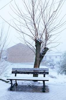 Cartolina di natale di una panchina e un albero pieno di neve