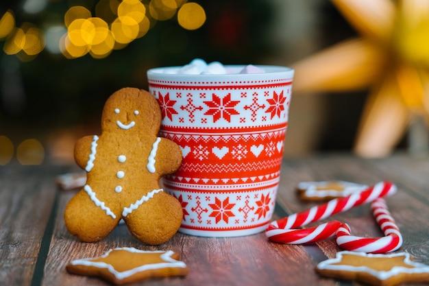 Cartolina di natale con la tazza rossa dell'uomo di pan di zenzero con l'ornamento di natale su bokeh leggero dall'albero di natale e dalle caramelle a strisce rosse di feste.