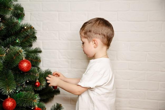 Famiglia di preparazione al natale che decora l'albero di natale con gli ornamenti