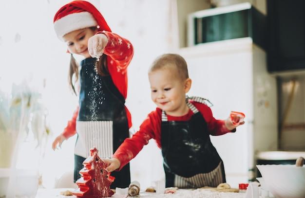 Preparazione natalizia di due fratelli che producono biscotti vestiti in abiti rossi con cappello santa