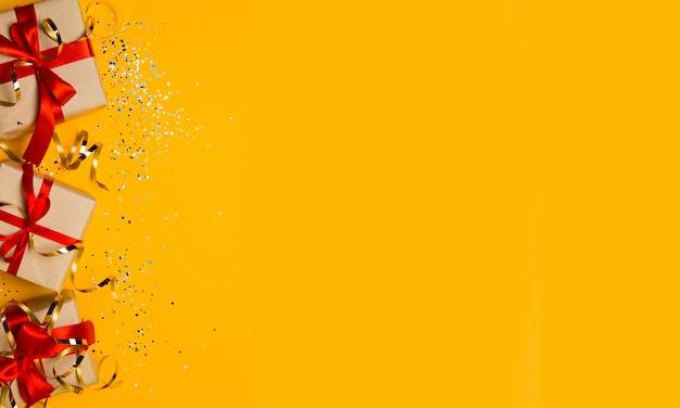 Regalo di natale o scatole con fiocchi rossi e coriandoli su una presentazione pastello giallo.