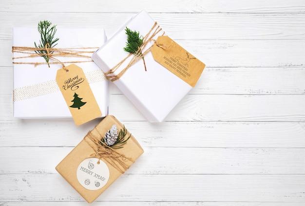 Regalo di natale e decorazione di foglie di pino sul tavolo di legno bianco