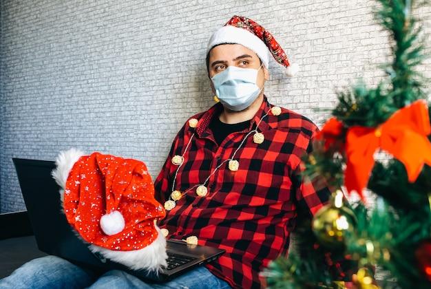 Regali di natale che danno. uomo in maschera medica che condivide regali tramite videochiamate. vacanze in isolamento. albero di capodanno e luci con decorazioni. famiglia e amici che festeggiano online.