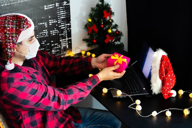 Regali di natale che danno. uomo che condivide i regali della scatola tramite videochiamate. vacanze in isolamento. albero di capodanno e luci con decorazioni. famiglia e amici che festeggiano online.