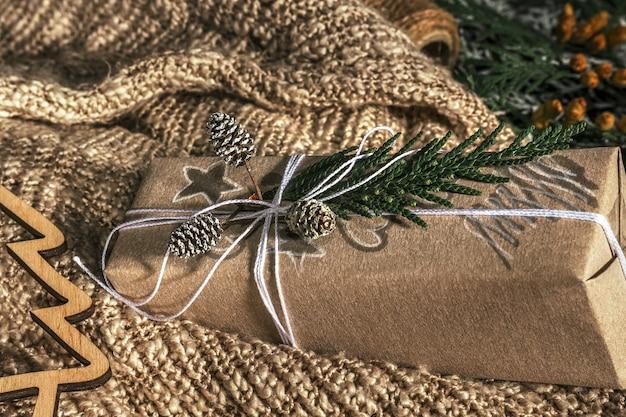 Regali di natale con confezione regalo decorata con pigne e ramoscelli su uno sfondo di tessuto di cotone, preparazione per le vacanze. regali di natale e capodanno. fatto a mano. messa a fuoco selettiva,